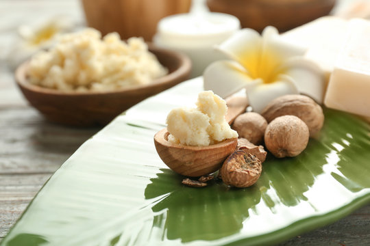 Bowl with shea butter, nuts and flower on plate