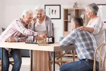Elderly people playing chess in nursing home