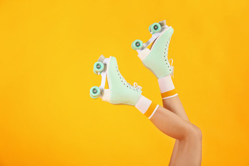 Legs of woman in roller skates on color background Wall mural