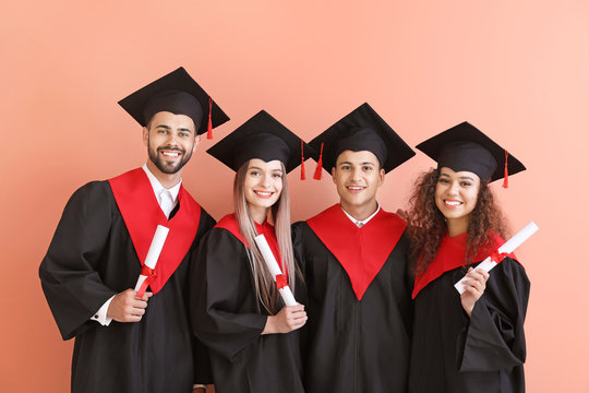 Young students in bachelor robes on color background