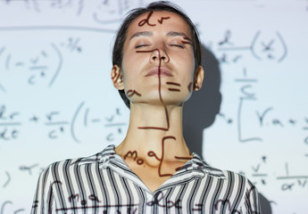 Serious attractive young woman in blouse inspired with mathematics standing in light of projector receiving calculations on wall and keeping eyes closed