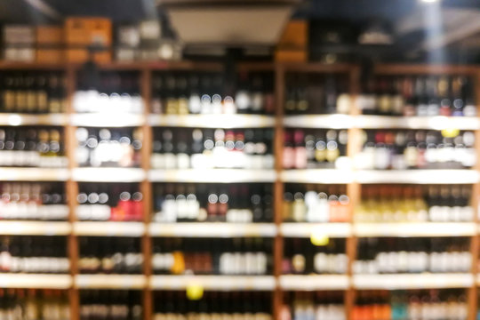Background blur of wine shelf rack at retail store