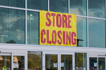 Store closing sign on business store front.