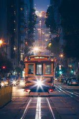 Fototapete - Classic view of historic traditional Cable Cars riding on famous California Street at night with city lights, San Francisco, California, USA