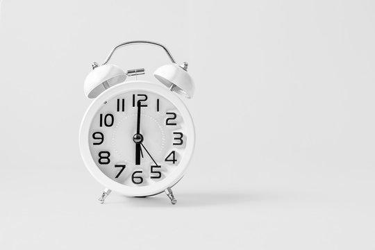 White vintage alarm clock on white background.
