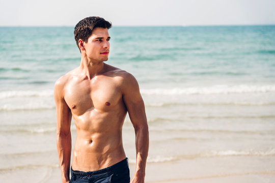 Portrait of smiling handsome sexy man showing muscular fit body standing on the tropical beach.Summer vacations