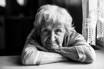 Close-up black and white portrait of a old woman at the table in home.