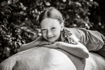Ein Mädchen liegt auf dem Pferderücken