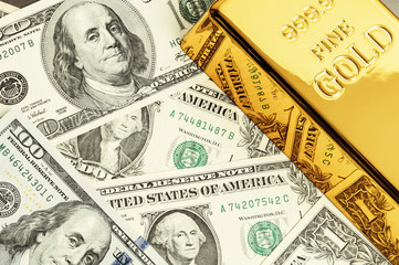 Gold metal ingot bullion on the background of dollar bills.