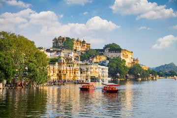 City Palace and tourist boat on lake Pichola. Udaipur, Rajasthan, India