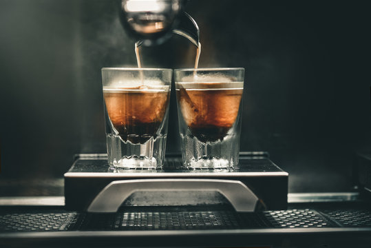 Professional coffee brewing. Coffee espresso. Close-up of espresso pouring from coffee machine to shotglasses.