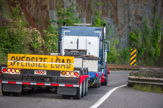 Big rig semi truck with sign oversize load behind flat bed semi trailer driving on the mountain road with rock wall on the side
