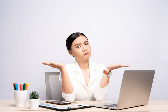Portrait of a confused woman sitting at office isolated over background