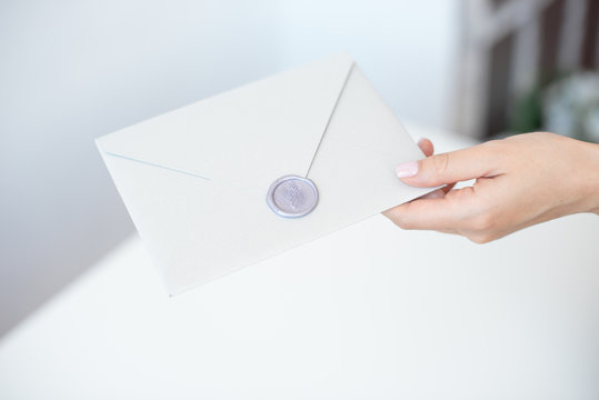 Close-up photo of female hands with wax seal with invitation envelope, gift certificate, postcard, wedding invitation card