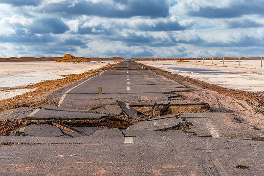 .broken asphalt road with cloudy sky in the middle of the  Lut desert,hottest desert in the world, also known like Kalut Desert