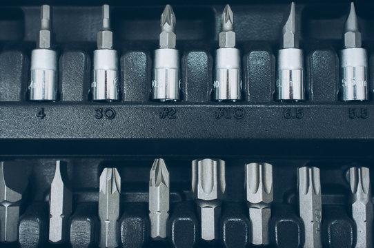 Toolbox socket organizer. Closeup of screwdriver bit set. Professional chrome instruments.