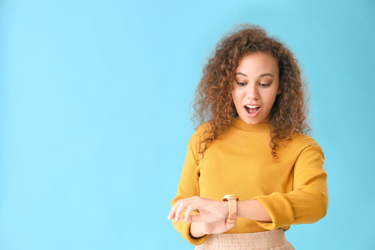 Beautiful African-American woman looking at watch against color background