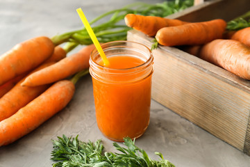 Jar of tasty carrot juice on grey table