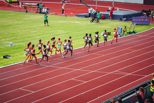 Female track and field race at athletics stadium. Professional female runners. Photo for athletics competition at summer olympic game Tokyo 2020.