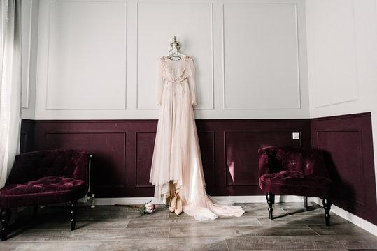 White wedding dress hanging in the bedroom. White bride dress