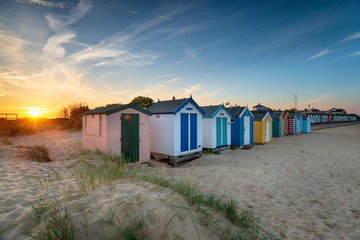 Sunset over a row of beach huts at Southwold