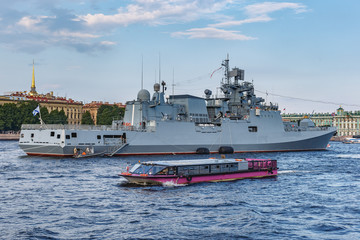 warship and tourist boats on the Neva River against the blue sky and the city