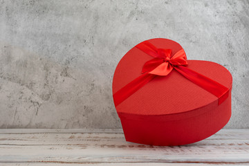 Red heart shape gift box on grey background. With copy space