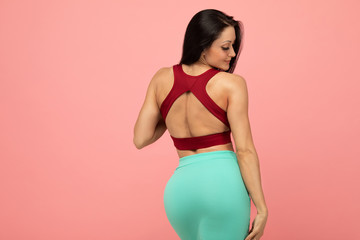 Beautiful happy brunette young woman posing in red bra and green skirt. Ideal slim sexy body. Pink background.