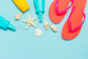 Wall Mural - Summer beach sea accessories. Coral flip flops, shells, starfish, yellow sunscreen bottle, body spray on blue background top view flat lay copy space. Summer background Holiday vacation travel concept