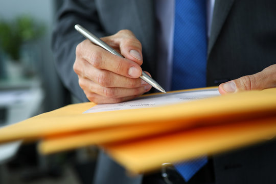 Male clerk in suit and tie at workplace hold in hands silver pen filling out application form