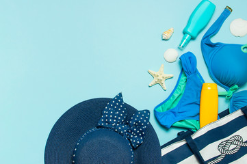 Wall Mural - Summer sea accessories. Beach bag Coral flip flops swimsuit female straw hat shells starfish sunscreen bottle body spray on blue background top view flat lay. Summer background. Holiday travel concept