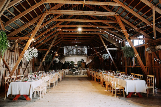 Interior of an old wooden hall with decorated tables.