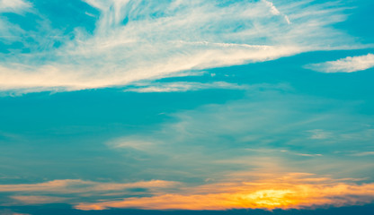 Beautiful blue and golden sky and clouds abstract background. Yellow-orange clouds on sunset sky. Warm weather background. Art picture of sky at sunset. Sunset and fluffy clouds for inspiration.