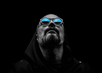 Bald man with a gray beard in sunglasses on a dark background. The concept of hope.