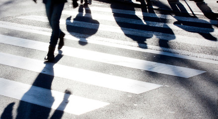 Blurry zebra crossing with pedestrians making long shadows Fotomurales