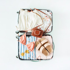 Hand luggage with bikini, sunglasses, slippers, retro camera and dress on white background. Flat lay, top view travel vacation fashion composition.