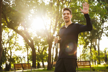 Handsome cheerful young sports fitness man standing in green park nature holding bottle with water...