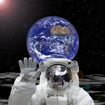 Astronaut posing on alien land. Earth on the backdrop. The elements of this image furnished by NASA.