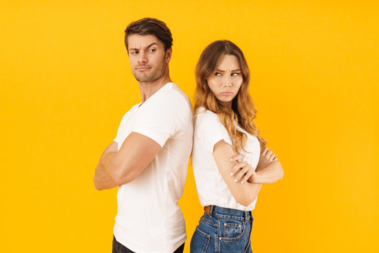 Portrait of serious offended couple man and woman in basic t-shirts standing back to back with arms folded in quarrel
