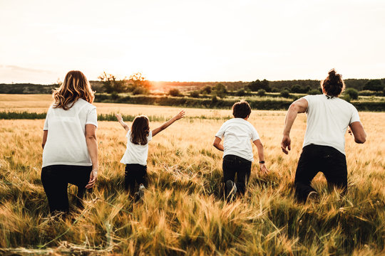 Happy family running through the countryside. Family having fun field