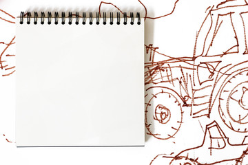 Mockup image: a notebook on a spiral with white square sheets on the background of a picture with tractors and abstractions, which is hand-drawn with markers. Kid's style drawing. Place for text