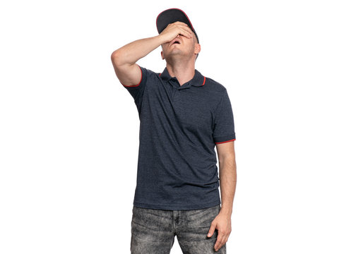 Unhappy Delivery man in gray t-shirt and cap. Studio portrait of tired caucasian handsome guy. Sad courier isolated on white background.