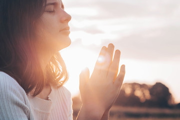 Teenager Girl closed her eyes, praying in a field during beautiful sunset. Hands folded in prayer concept for faith, spirituality and religion. Peace, hope, dreams concept