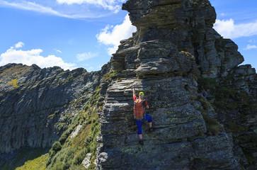 Hiker climbing on a ridge in the mountains of Ticino, Switzerland. Via Alta Verzasca.