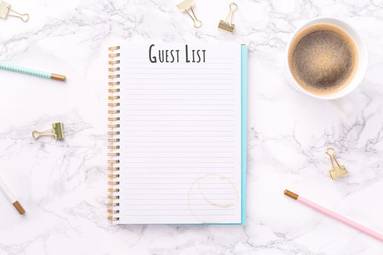 Festive golden stationary and coffee on white Guest List wording. Copy space. Top view. Horizontal