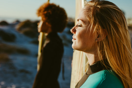 Profiles of two female surfers on beach in sunlight