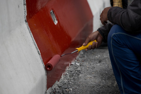 Construction worker painting concrete floor with red paint