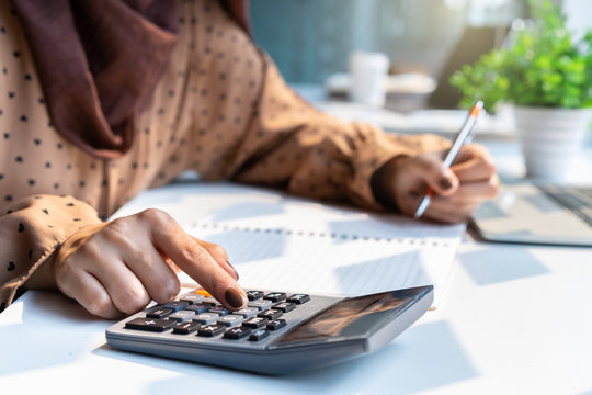 Casual accountant or banker woman hand using calculator at workplace.