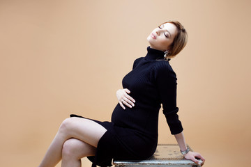85e06e16d3c20 Young beautiful pregnant woman in black clothes hugs her tummy on a beige  neutral background.