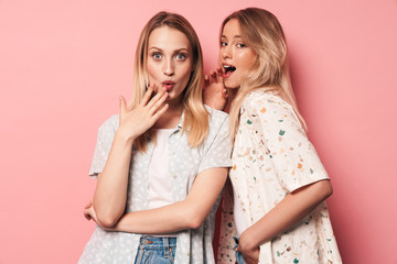 Surprised shocked pretty blondes women friends posing isolated over pink wall background.
